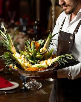 Cameriere in possesso di un piatto di mix di frutta con porzione originale