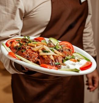 Waiter holding a platter of iskender kebab served with yoghurt and vegetable slices