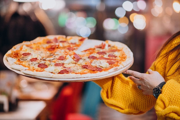 Официант держит вкусную пиццу с салями на тарелке