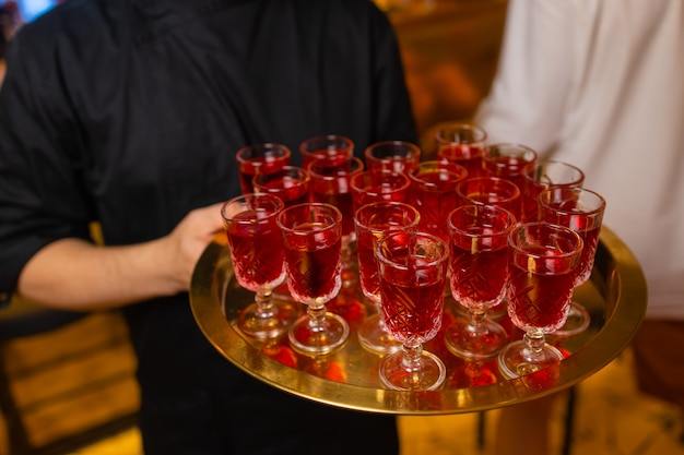 Waiter holding tray with aperol spritz cocktail summer drink