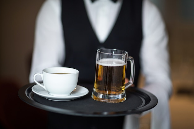 Waiter holding tray with beer