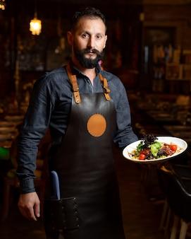 Официант держит овощную салатную тарелку с кукурузным орехом, листьями салата, вишней и вялеными томатами