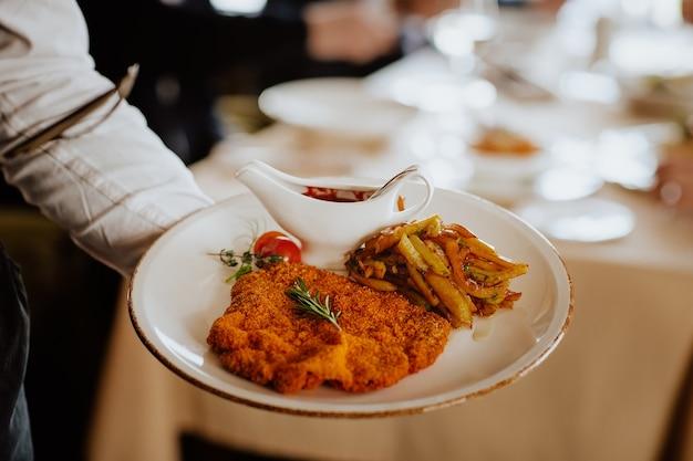 Официант держит венский шницель с жареным картофелем, розмарином и кетчупом в ресторане.