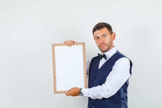 Cameriere che tiene bordo bianco in camicia, gilet, farfallino e sembra serio. vista frontale.