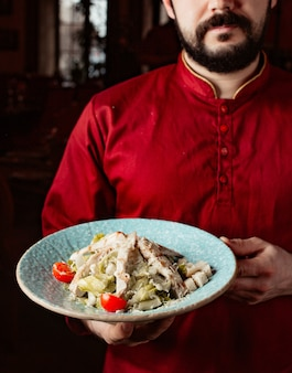 Waiter holds caesar salad with chicken lettuce cherry tomato parmesan and bread stuffing
