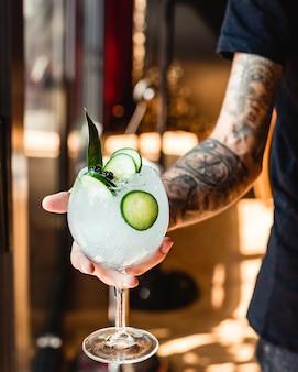 Il cameriere tiene un bicchiere di acqua ghiacciata di cetriolo guarnita con una foglia
