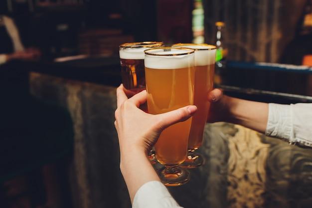 ウェイターはバーやパブで手にビールのグラスを保持しています。ビールグラス。 Premium写真