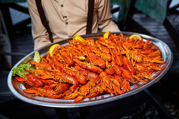 The waiter holds a large tray of red boiled crayfish with lemon