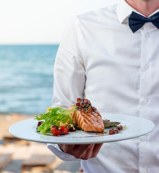 Waiter holds a plate of grilled smoked salmon with lettuce, tomato, pepper