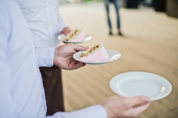 The waiter holds plates with pieces of cake
