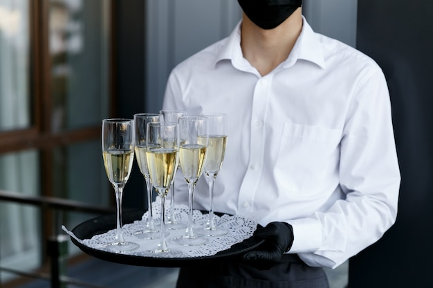 The waiter holds a tray with glasses of champagne