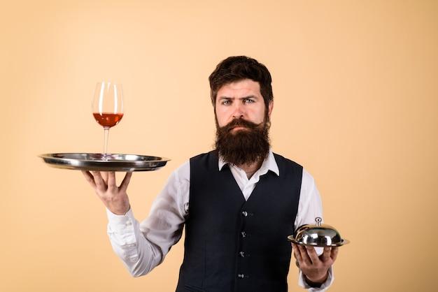 Официант держит поднос с вином и металлической крышкой-крышкой, концепция дворецкого профессионального кейтеринга
