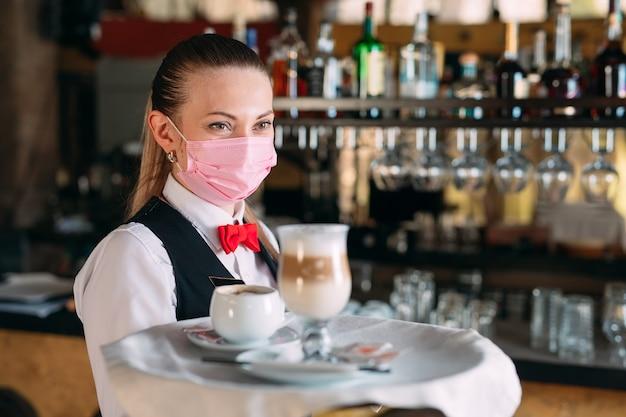 Официант в медицинской маске подает кофе латте