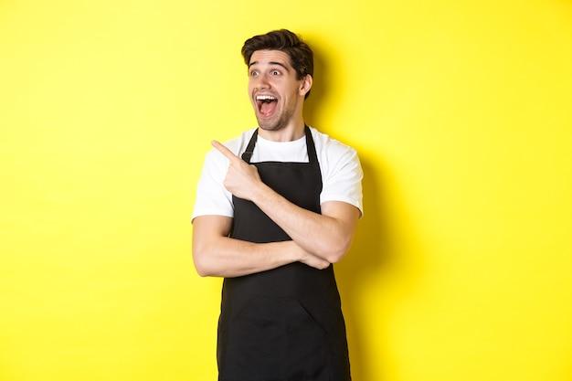 프로모션 제안을 확인하고 손가락을 가리키고 노란색 배경 위에 서있는 로고를 왼쪽으로보고 검은 앞치마에 웨이터.