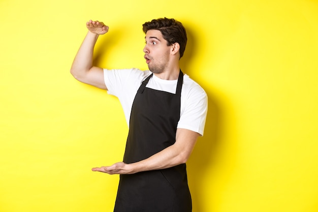 Официант в черном фартуке с изумлением смотрит на что-то большое, держащее большой предмет, стоящий над желтой спиной ...