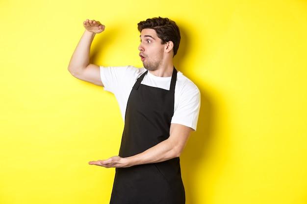 Официант в черном фартуке с изумлением смотрит на что-то большое, держит большой предмет и стоит над желтой стеной