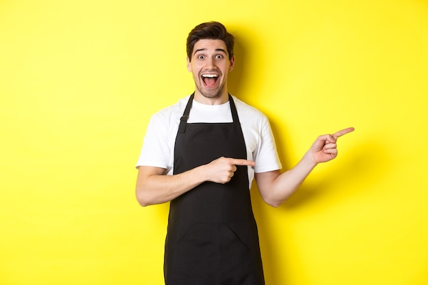 검은 앞치마를 입은 웨이터가 손가락을 오른쪽으로 가리키며 광고를 보여주고 흥분한 미소를 지으며 노란색 배경에 서서