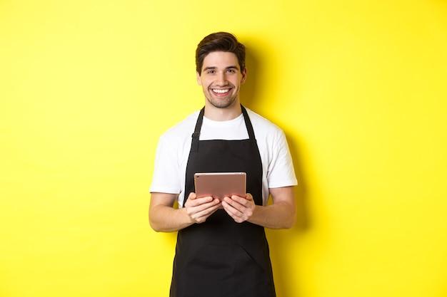 주문을 받고, 디지털 태블릿을 들고 웃고, 노란색 배경 위에 서있는 검은 앞치마에 웨이터.