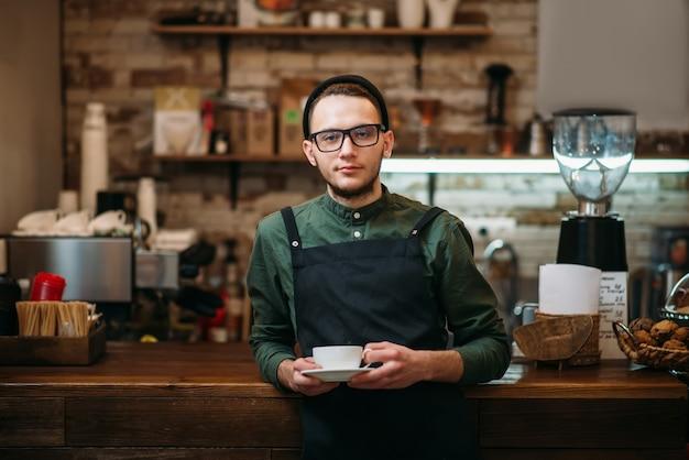 Официант в очках с чашкой кофе в руках оперся локтями о барную стойку.