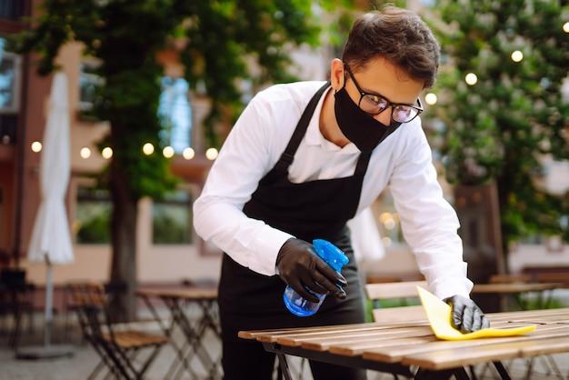 次の顧客のためにレストランのテーブルを消毒する保護マスクと手袋のウェイター。