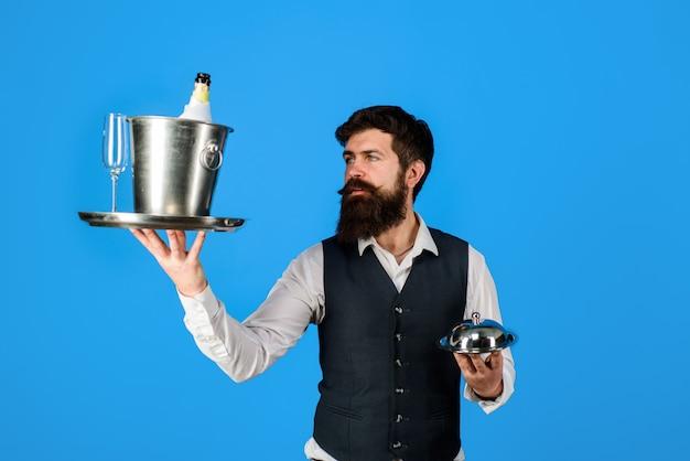 금속 cloche를 들고 웨이터를 제공하는 유니폼 레스토랑에서 레스토랑 전문 웨이터의 웨이터