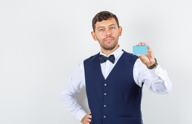 Официант в рубашке, жилете держит визитную карточку с рукой на талии и выглядит услужливо, вид спереди.