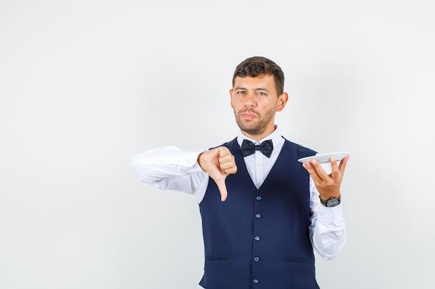 Официант в рубашке, жилете держит пустую тарелку большим пальцем вниз и выглядит недовольным, вид спереди.