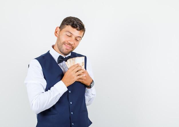Официант в рубашке, жилете держит деньги на груди и выглядит обнадеживающим, вид спереди.
