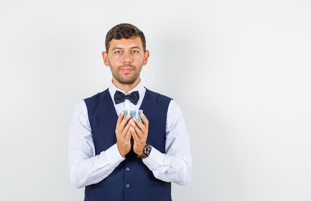 Официант в рубашке, жилете держит коробку для часов и выглядит позитивно, вид спереди.