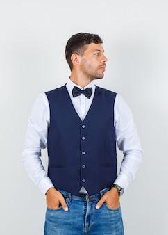 Официант в рубашке, жилете, джинсах смотрит в сторону с руками в карманах и выглядит мило, вид спереди.