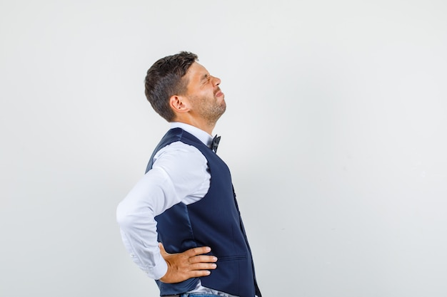 Официант в рубашке, жилете, джинсах страдает от болей в спине и выглядит больным.