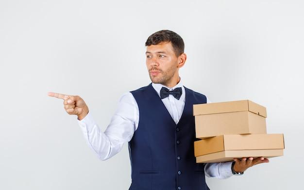 Официант в рубашке, жилетке с картонными коробками, вид спереди.