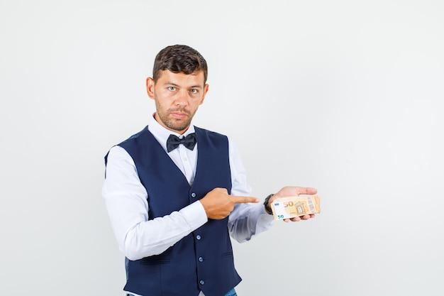 Официант в рубашке, жилете, указывая пальцем на банкноты евро и серьезный вид спереди.