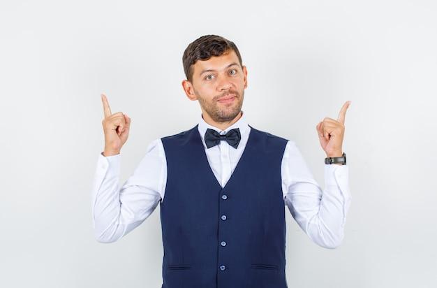 シャツを着たウェイター、人差し指を上に向けて元気に見えるベスト、正面図。