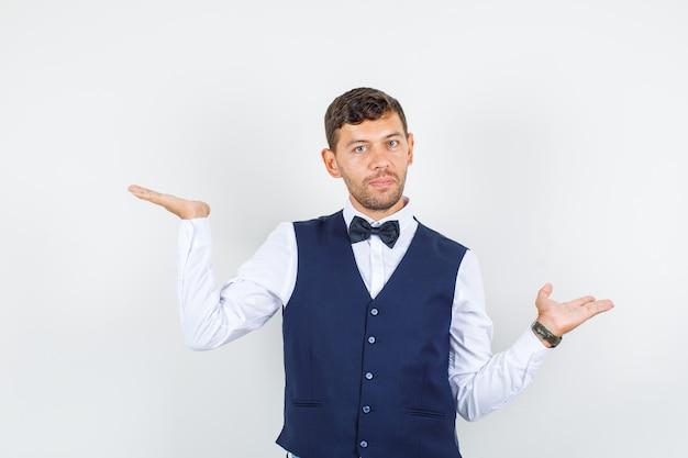 シャツを着たウェイター、何かを持って真剣に見えるように開いた手のひらを上げるベスト、正面図。