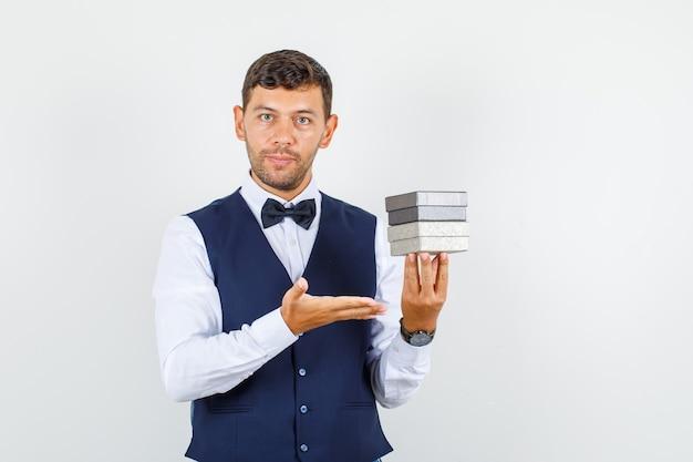 Официант в рубашке, жилете показывает коробки для часов и выглядит уверенно, вид спереди.