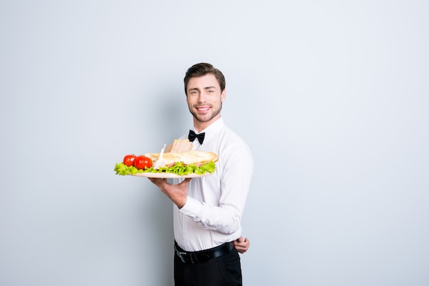 Waiter is holding a large tray with an appetizer
