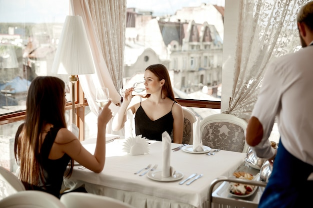 Waiter is serving dinner for two pretty friends women at the elegant restaurant