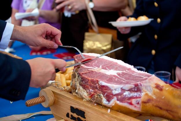 Waiter is slicing ham