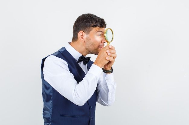 Waiter looking through magnifying glass in shirt, vest front view.
