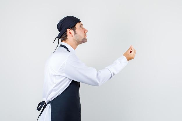 ウェイターは見上げて、制服、エプロン、自信を持ってイタリアのジェスチャーをしています。 。