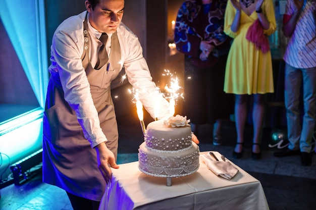 The waiter makes a wedding cake with roman candles