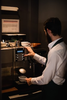 Waiter making cup of coffee from espresso machine
