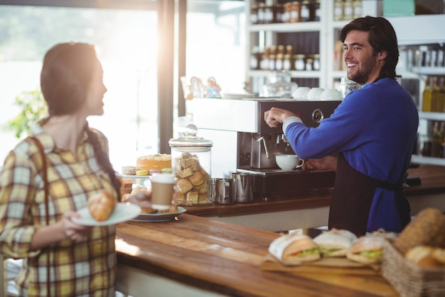 Waiter making cup of coffee while interacting with customer