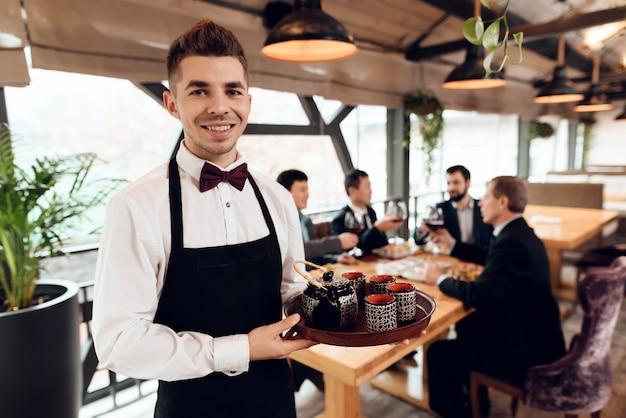 アジアのビジネスマンのためのお茶を作るウェイター