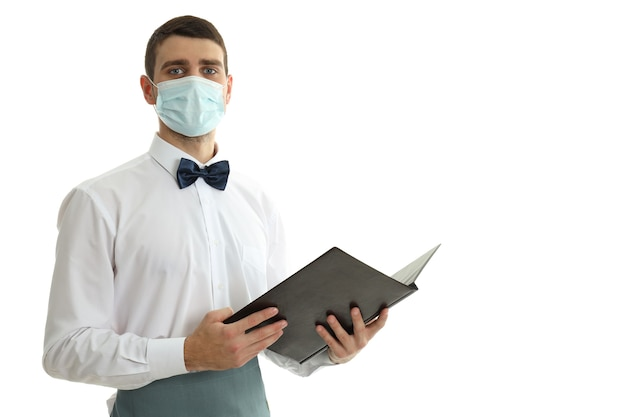Waiter in mask holds menu, isolated on white background.
