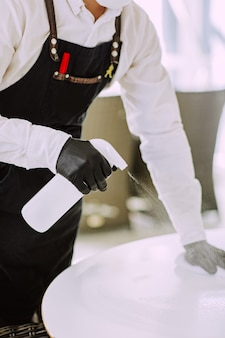 Waiter in medical mask and gloves cleaning white table