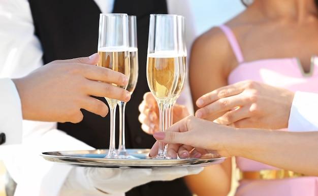 Официант предлагает шампанское гостям на вечеринке, вид крупным планом