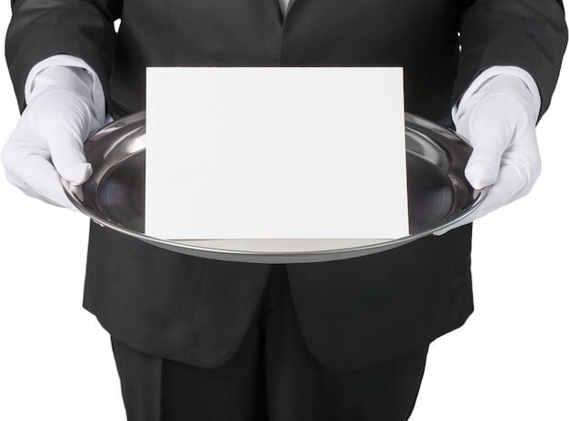 胴体の前の銀のトレーにノートカードを持ったタキシードを着たウェイターまたは執事。