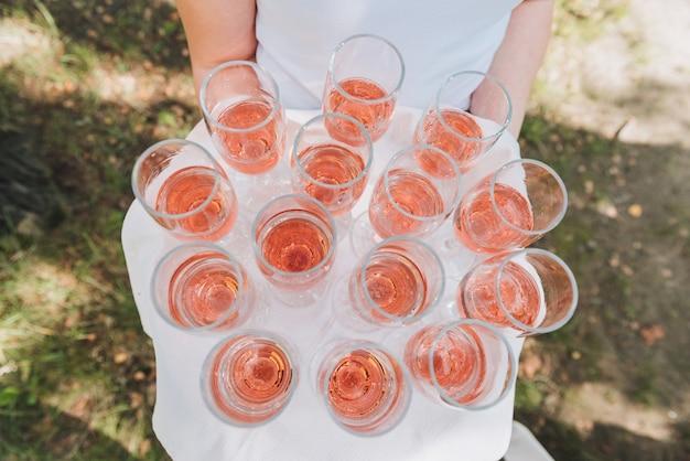 結婚披露宴でゲストのためにバラのスパークリングワインのグラスのトレイを保持しているウェイターまたはサーバー